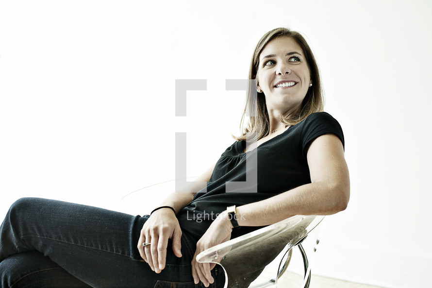 A woman sitting in a chair smiling