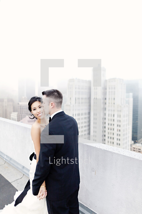 groom kissing his bride on the cheek on top of building in city fog wedding love romance marriage