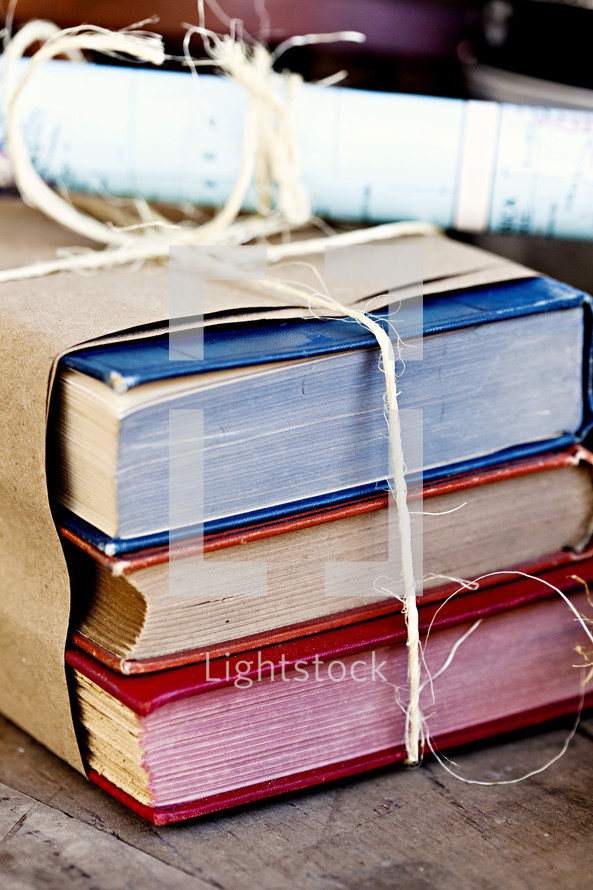 Books wrapped in brown paper and tied with twine.