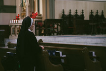 A roman Catholic nun praying the rosary in a church