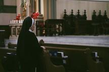 A roman Catholic nun praying the rosary in a church