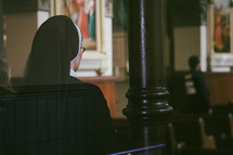A Catholic nun standing in the back of a church