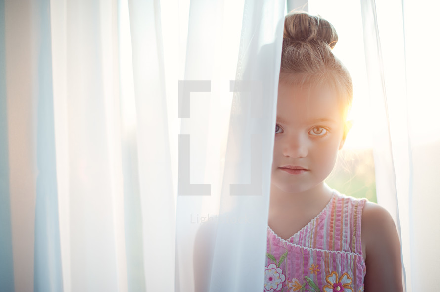 girl child standing in curtain sheers at a window