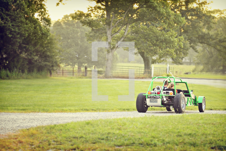 couple driving dune buggy down country lane - trees
