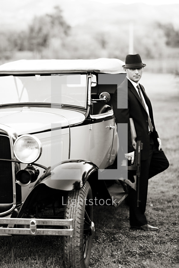 gangster man in front of an old car holding a tommy gun