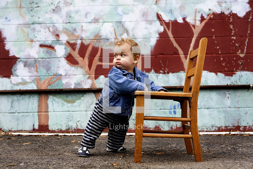 toddler boy holding onto a chair to stand