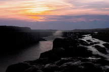 cliffs and waterfall at sunset