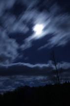 clouds in the night sky and the glow of a full moon