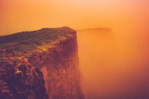 red rock cliff under an orange sky