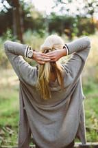a woman braiding her blonde hair outdoors