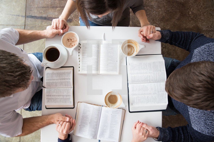 study group sitting at a table discussing the Bible and holding hands in prayer