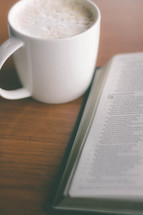 coffee cup and an open Bible