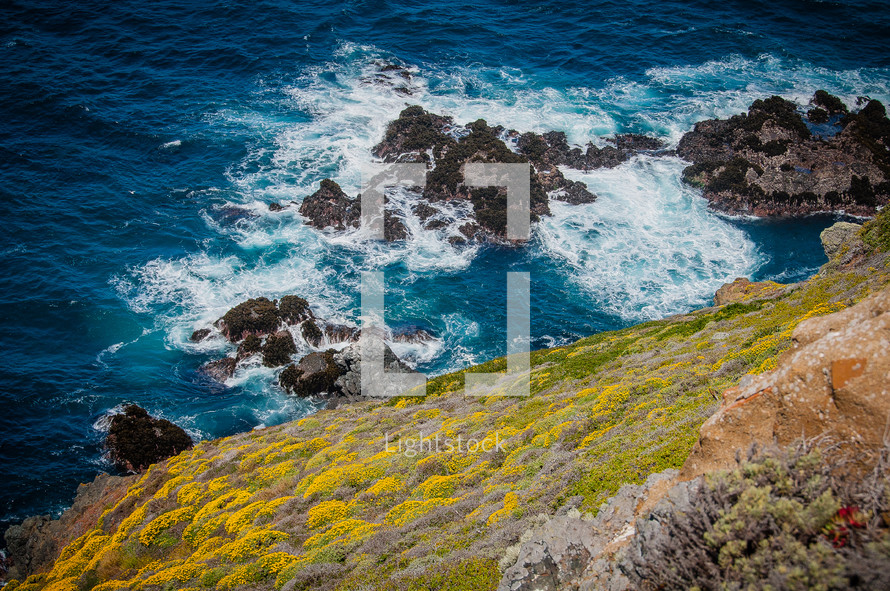 looking down at waves crashing into rocks in the ocean