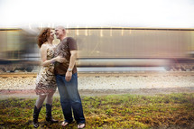 Couple embracing in front of moving train.