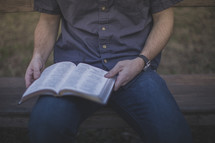 A man sitting on a bench reading the Bible