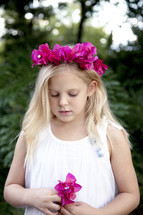 Girl in white dress with pink flowers in her hair holding a pink flower while praying.