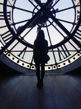 a woman standing in front of a clock in a clock tower