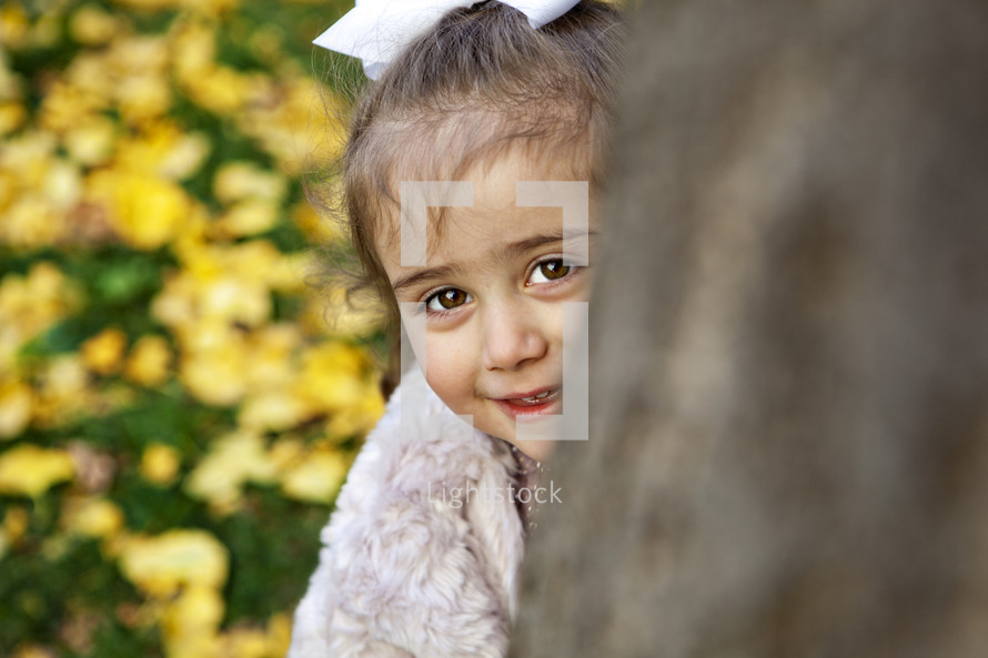 girl peeking around a tree