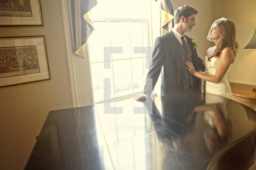 bride and groom standing by grand piano and window