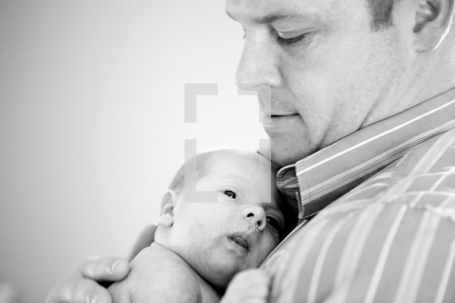 father holding his newborn baby