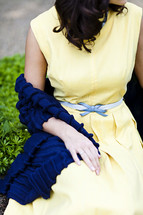 A young woman sitting yellow dress summer spring blue shawl