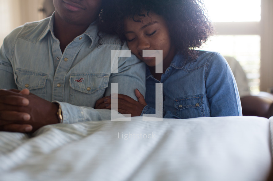 a couple in prayer beside a bed
