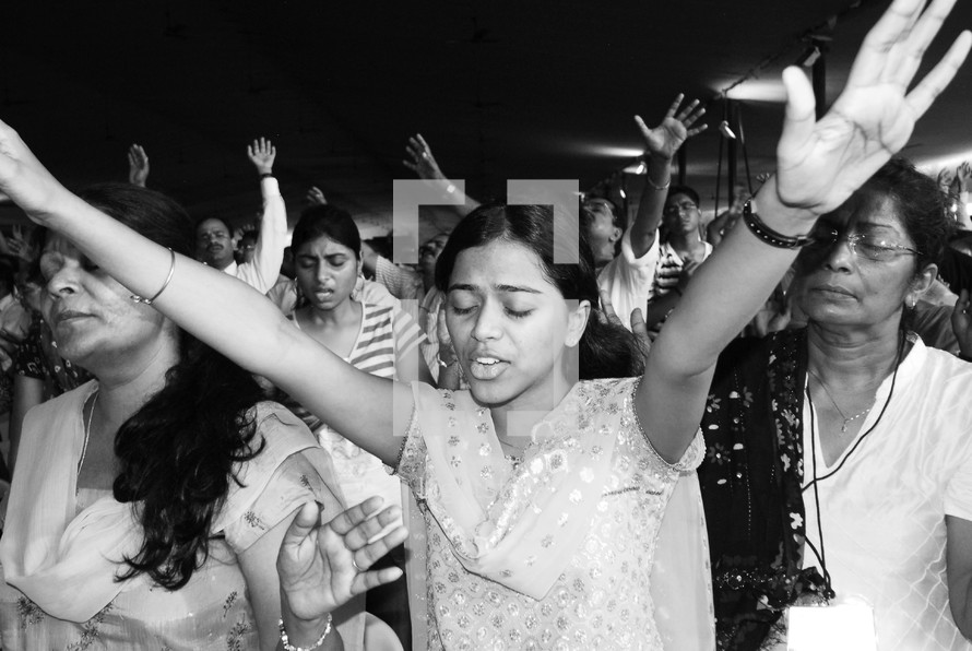 Indian woman with her hands raised in worship to God
