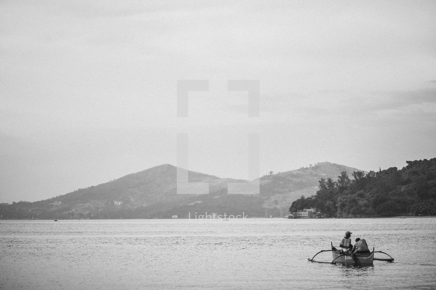 Two men paddling a boat on a lake