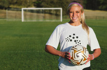 teen girl holding a soccer ball