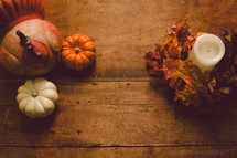 Turkey figurine, miniature pumpkins, and a candle with a wreath of fall leaves on a wooden table -- Thanksgiving decor.