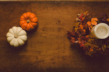 Miniature pumpkins and a candle with a wreath of fall leaves on a wooden table -- Thanksgiving decor.