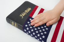 Hand on a Holy Bible wrapped in an American flag.