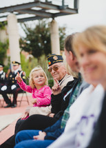 A Veteran holding his granddaughter in his lap