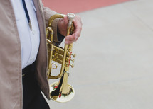 man walking carrying a trumpet
