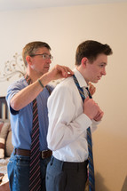 a father helping his son put on a tie