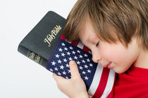 Boy praying over a Holy Bible wrapped in an American flag.