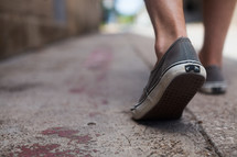shoes walking on a sidewalk