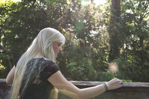 teen girl with long blonde hair looking over a railing into a forest