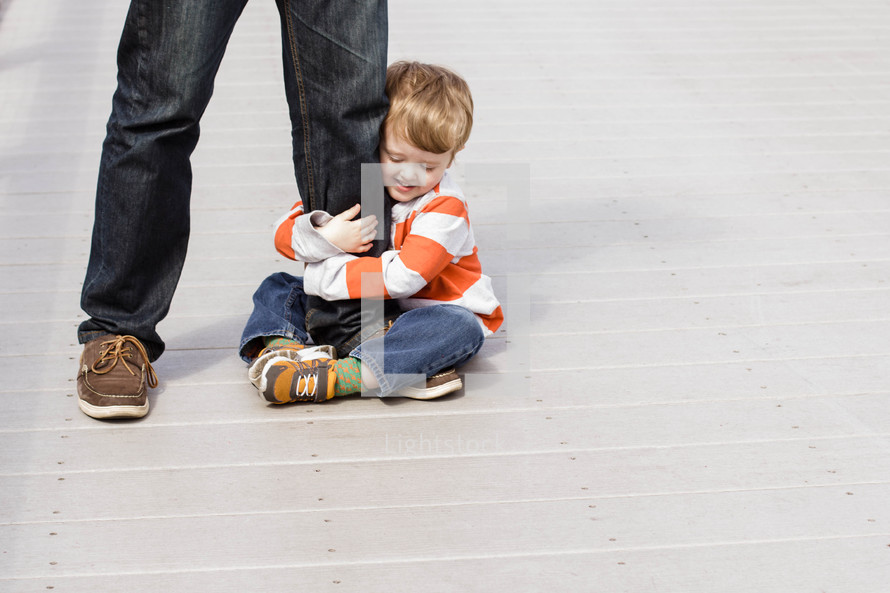 toddler boy hugging father's leg