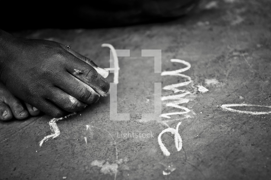 A child writes on the ground using chalk