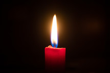 flame on a red candle in darkness