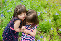 Two young girls standing in a weedy field, hugging