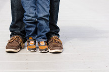 Legs and feet of a man and boy standing together.