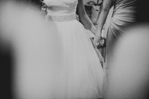 A bride and bridesmaid holding hands at a wedding