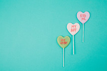 Three Valentine candy hearts on an aqua background.