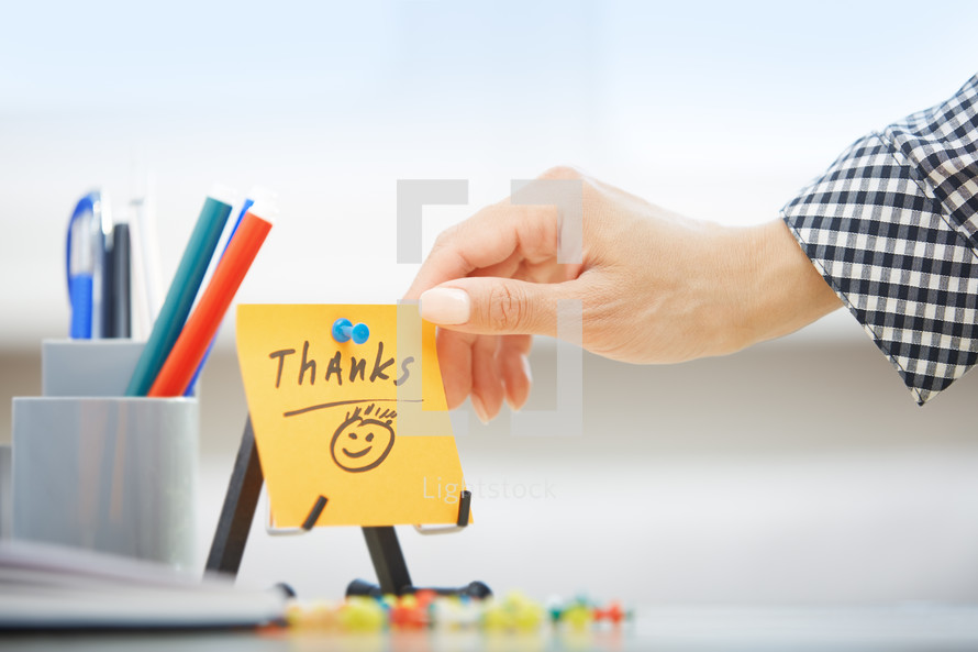 a woman reaching for a sticky note