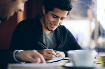 man writing in a journal at a Bible study