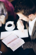 man holding and reading a Bible during a Bible study