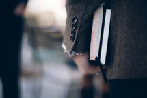 man carrying a Bible and journal at his side heading to a Bible study