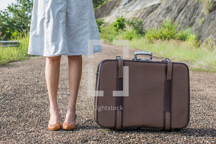 woman legs standing next to luggage